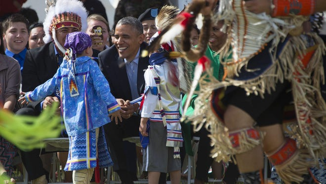 US President Barack Obama and Chairman of the Standing Rock Sioux Tribal Nation David Archambault II (left) talk with young performers during the Cannon Ball Flag Day Celebration in Cannon Ball, N.D., on June 13, 2014.
