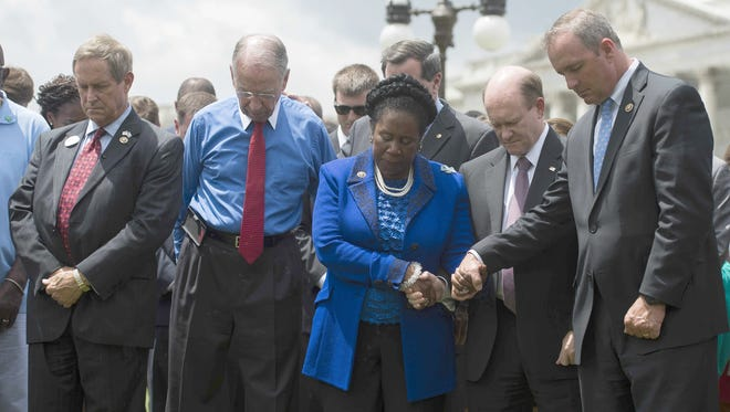US Congressman Jeff Duncan (R), R-South Carolina, holds hands with Senator Chris Coons (2nd R), D-Deleware, and Congresswoman Shelia Jackson Lee (C), D-Texas, as they stand with Senator Chuck Grassley (2nd L), R-Iowa, and Congressman Joe Wilson (L), R-South Carolina, in front of the US Capitol in Washington, DC, June 18, 2015, during a moment of silence for the nine killed in a church shooting in Charleston, South Carolina.   AFP PHOTO/JIM WATSON        (Photo credit should read JIM WATSON/AFP/Getty Images)