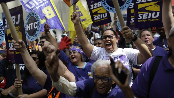 Activists cheer during a rally Wednesday after the New York Wage Board endorsed a proposal to set a $15 minimum wage for workers at fast-food restaurants with 30 or more locations.