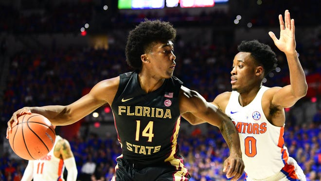 FSU junior guard Terrance Mann holds off Florida freshman guard Mike Okauru during the first half at the O'Connell Center in Gainesville.