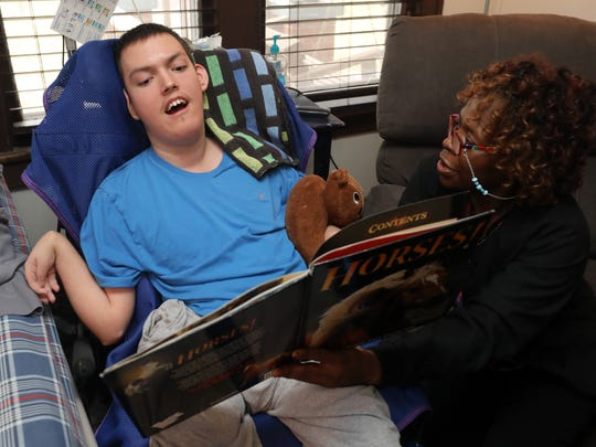 Carlene Beard, an LPN, reads a book with Tristen Shackelford while providing treatment for him at his home on February 16, 2018.