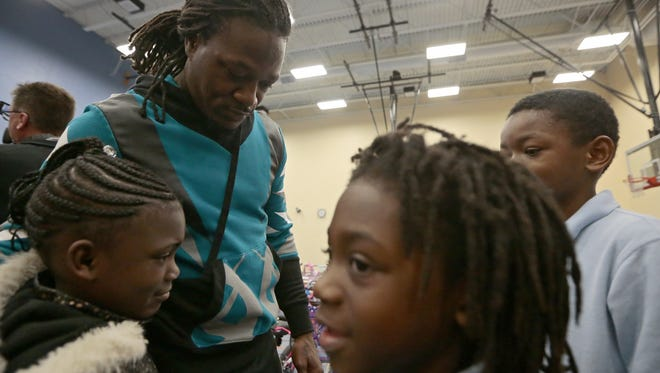 Cincinnati Bengals cornerback Adam Jones hugs students as they line up to thank him for his gift to the children at Lincoln Heights Elementary School in Lincoln Heights, Ohio, on Tuesday, Dec. 13, 2016. Jones collaborated with team mates Vontaze Burfict and Andrew Whitworth to give away more than 250 bikes to the students in a surprise assembly.