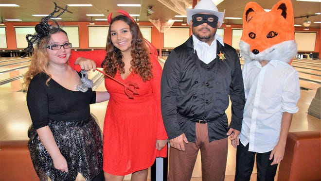 "Jessica Restrepo, left, Nastasia Torres, Mauricio Restrepo and Isiah Torres dressed for the Halloween-themed ""Bowl to Build"" scholarship fundraiser for Indian River Habitat for Humanity at Vero Bowl on Oct. 29."