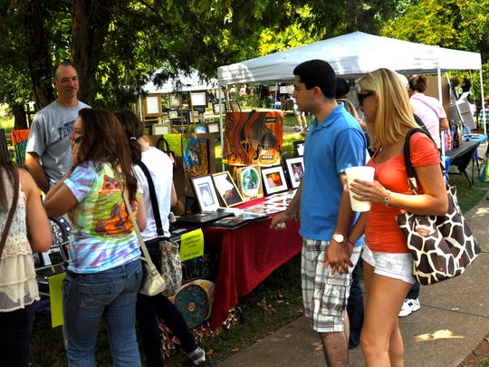 A crowd gathers to look over the offerings at a past Greenway Arts Festival. This year's event will be Tuesday along the trail at Old Fort Park.