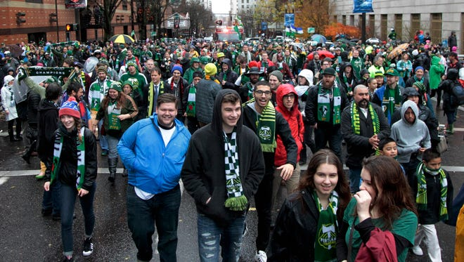 Fans follow the Portland Timbers during the MLS champions parade through Portland, Ore., Tuesday, Dec. 8, 2015.  The Timbers defeated the Columbus Crew 2-1 Sunday in the MLS Cup soccer final.