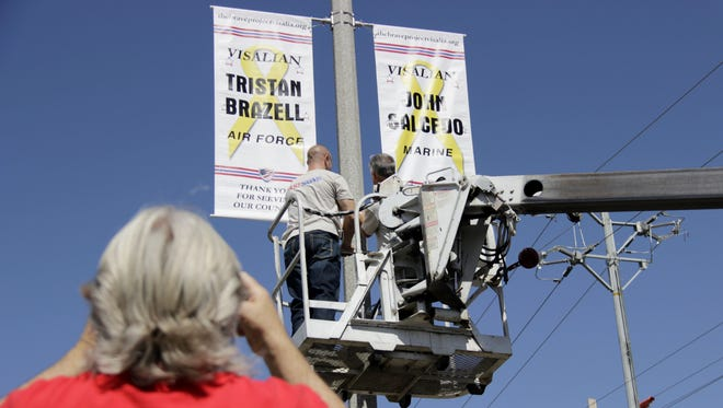 Bart Lang snaps photos as his grandson's Brave Project banner is installed near the intersection of Caldwell Avenue and Demaree Street in Visalia on Wednesday morning.