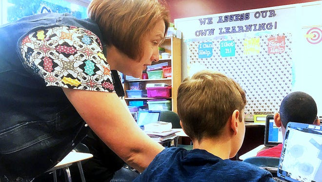Broadway Academy teacher Alisson Moore assists 7th grade students with new computer technology.