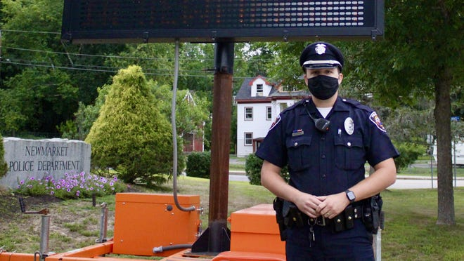 Newmarket police officer Zach Wedgeworth wears a mask, setting an example and reminding residents and visitors of the town's emergency mask mandate to reduce COVID-19 spread. Durham has a similar mandate, while Portsmouth and Exeter are considering mask mandates.
