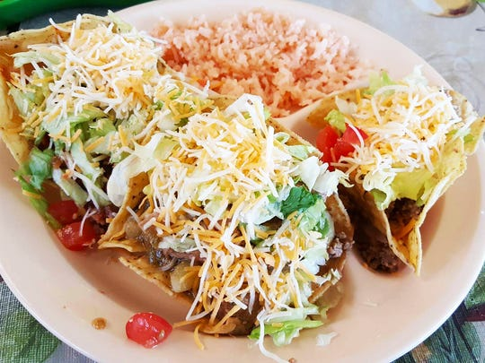 Tostados compuestas from Bravo's Cafe. The plate comes with rice and three tostados — red, green and ground beef.