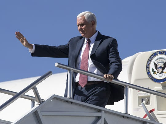 Vice President Mike Pence waves on Tuesday, Oct. 3, 2017, at Phoenix Sky Harbor Airport, as he steps off Air Force Two.
