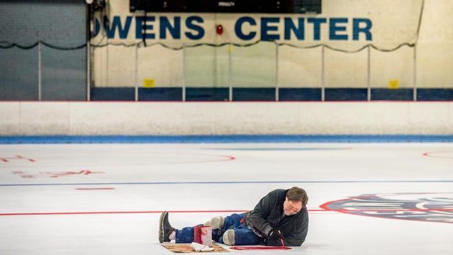 Maintenance foreman Steve Wisher paints a neutral zone faceoff spot on one of the ice-free rinks at Owens Center in Peoria. Both rinks at the center have been de-iced and have undergone maintenance since the COVID-19 shutdown.