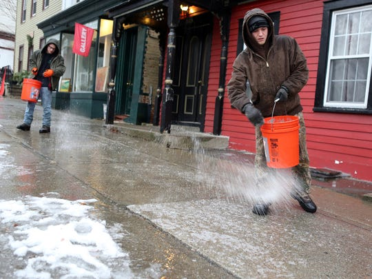 Rich Larsen and John Peragine spread salt along a sidewalk in Cold Spring Jan. 12, 2015. Sleet and freezing rain forced many northern Westchester and all of Putnam's public schools to close.