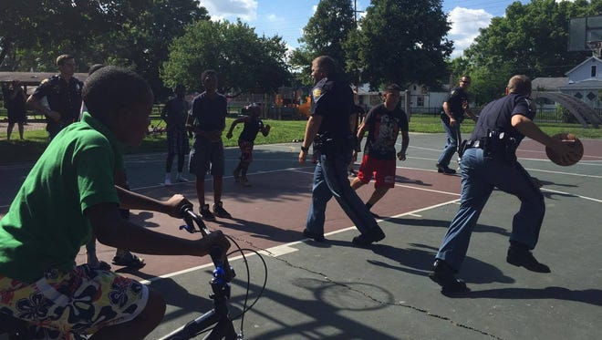 Four Indiana State Police troopers accept the challenge of kids in Lafayette's north end for a pickup basketball game Saturday evening at Linnwood Park.