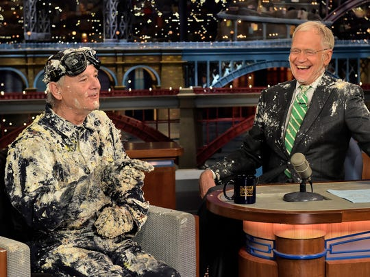 """Actor Bill Murray, left, talks with host David Letterman after emerging from a cake to say goodbye Tuesday on the set of the """"Late Show with David Letterman"""" in New York."""