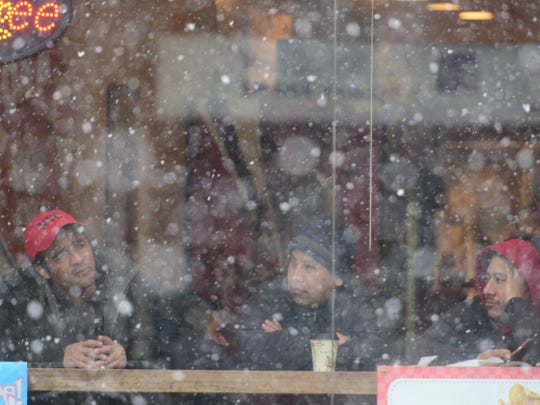 Three men watch the snow fall from a coffee shop on