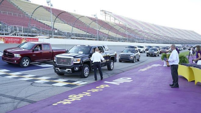 Onsted High School Principal Kevin Ohrman, at left, greets students during a drive-through diploma hand off Friday evening, during the high school's commencement ceremony, which took place on the race track of Michigan International Speedway.