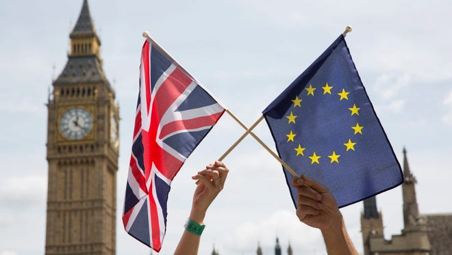 Members of the public hold flags at a stay-in, pro-EU Referendum event in Parliament Square in London on June 19, 2016.