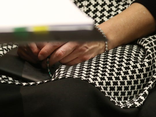 Laura Rideout holds some type of beaded item in her hands during the hearing.