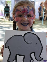 Julie Murray shows the elephant painting she made. Photographed July 18, 2015 at the Salem Art Fair & Festival at Bush's Pasture Park.