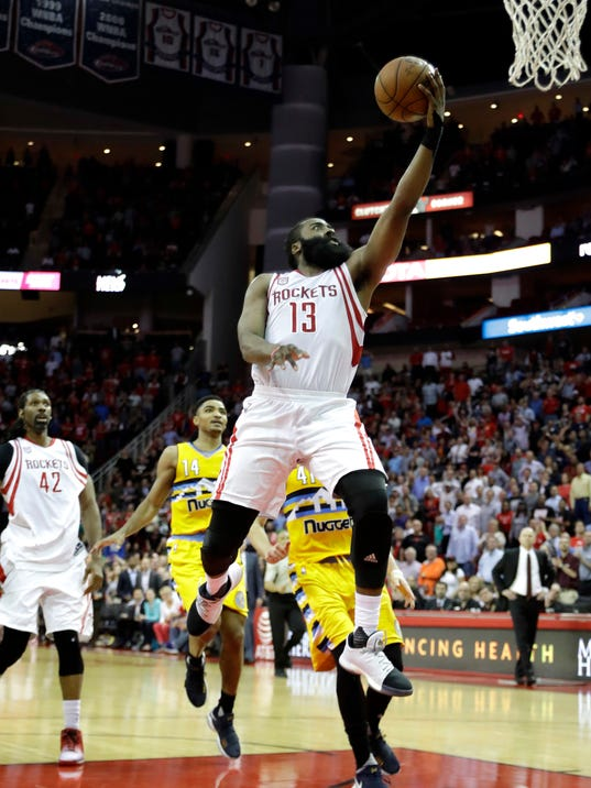 Houston Rockets' James Harden (13) goes up to score the game-winning basket during the second half of an NBA basketball game against the Denver Nuggets Monday, March 20, 2017, in Houston. The Rockets won 125-124. (AP Photo/David J. Phillip)