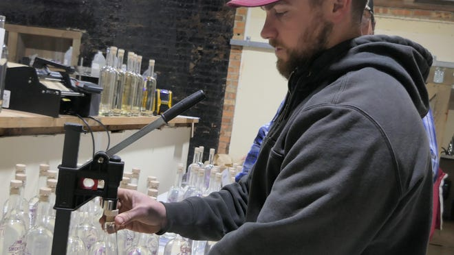Shane Von Stohe places the plug on his Wild Plum Flavored Vodka at his company, Smoky Valley Distillery, in Marquette.