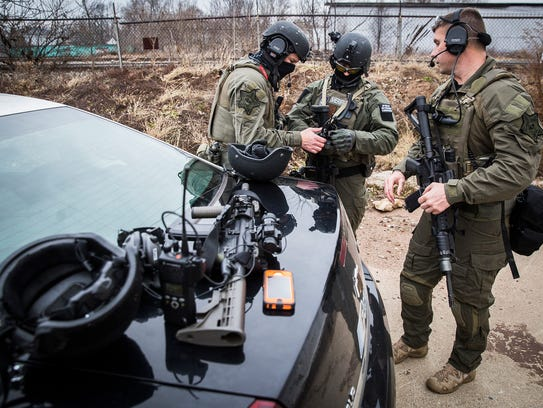 SWAT team members gear up while waiting for warrant