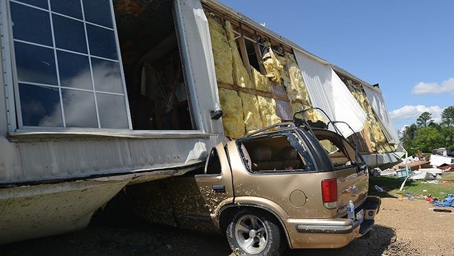 A mobile home was flipped upside-down and came to rest on an SUV when a powerful tornado tore through Highlands trailer park in Pearl, Miss.