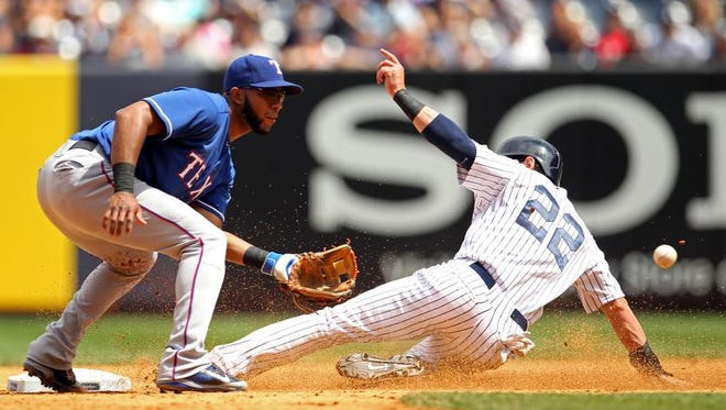 New York Yankees center fielder Jacoby Ellsbury (22) steals second base ahead of the throw to Texas Rangers shortstop Elvis Andrus (1) during the fifth inning at Yankee Stadium.