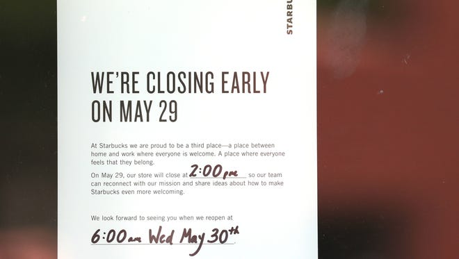 A sign to customers outside Starbucks in Red Arrow Park in Milwaukee says it will close at 2 p.m. Tuesday for an afternoon of anti-bias training.  The closure is part of a company-wide move toward racial reconciliation Tuesday as it closes 8,000 stores across the nation.  The training follows an incident at a Starbucks store in Philadelphia in April in which a manager called police on two African-American men who were quietly waiting for a friend.