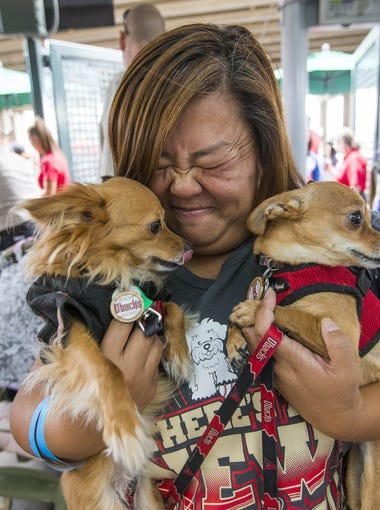 Cathi Macneil holds Trixie (left) and Chase while entering Chase Field for the Arizona Diamondbacks Bark at the Park promotion before playing against the Colorado Rockies in Phoenix May 1, 2016.