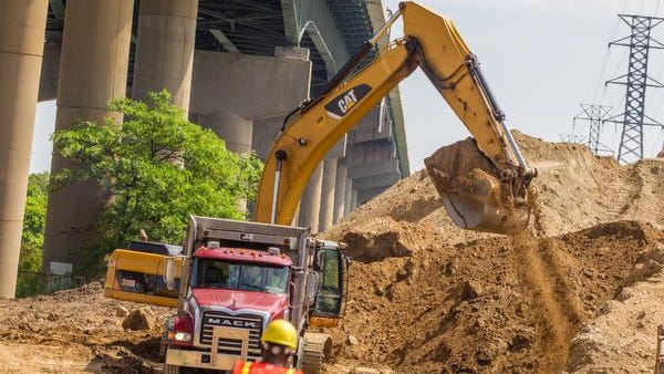 The Delaware Department of Transportation, contractors and engineers work to move stories-high piles of dirt near the Interstate 495 bridge over the Christina River in Wilmington, Del. They worry that the extra weight could have caused concrete piers to tilt.