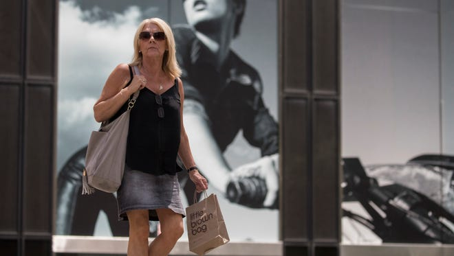 A pedestrian walks carrying a Bloomingdales' Little Brown Bag walks past a giant advertisement for Armani Exchange on Fifth Avenue in New York. On Tuesday, June 26, the Conference Board releases its June index on U.S. consumer confidence.