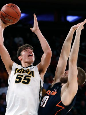 Iowa forward Luka Garza (55) shoots over Illinois forward Michael Finke during the second half of an NCAA college basketball game in the first round of the Big Ten men's tournament Wednesday, Feb. 28, 2018, in New York. Iowa defeated Illinois 96-87. (AP Photo/Kathy Willens)