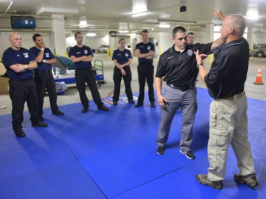 Instructor officers Rob Schreiber and Nick Tylutki demonstrate defending against a haymaker punch Tuesday as new recruits look on at the St. Cloud Police Department.