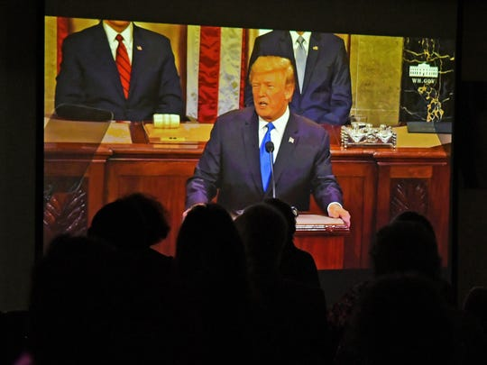 Local residents watch as President Donald Trump gives his State of the Union address.