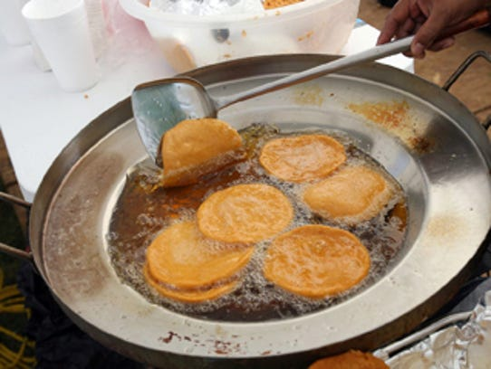 Gordita shells sizzle in oil at a festival. The hot