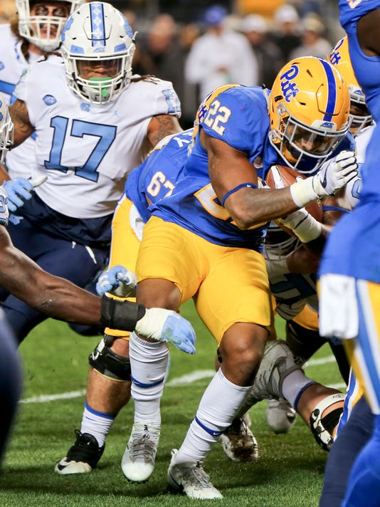 Pittsburgh running back Darrin Hall (22) follows blockers past North Carolina defensive end Dajaun Drennon (17) on his way to a touchdown during the second quarter of an NCAA college football game, Thursday, Nov. 9, 2017, in Pittsburgh. (AP Photo/Keith Srakocic)