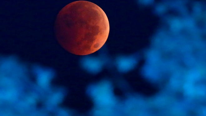 The Earth's shadow renders the moon during a total lunar eclipse over Milwaukee on Wednesday, Oct. 8, 2014.  The moon appears orange or red, the result of sunlight scattering off Earth's atmosphere. This is known as the blood moon.  (AP Photo/Milwaukee Journal-Sentinel, Mike De Sisti)
