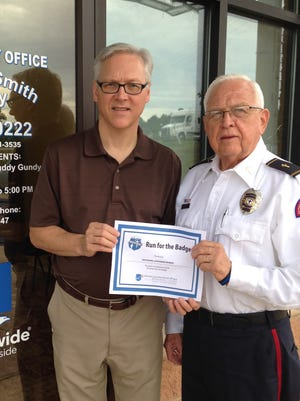 David McPhail, left, is presented with a certificate thanking him for his contribution to Run for the Badge by participant Nathan Barber.