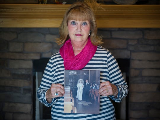 Vicky Burnett, of Evansville, holds a photo taken of her and her father on her wedding day on April 1, 1967, at her home in Evansville, Friday, Sept. 7, 2016. Burnett's father, Paul Roedel was murdered on July 5, 1971, the case remains unsolved.
