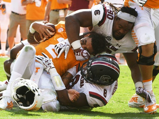 Tennessee quarterback Jarrett Guarantano's (2) helmet falls off as he is tackled by South Carolina defensive lineman Taylor Stallworth (90)  and South Carolina defensive lineman D.J. Wonnum (8) during the second half of a Tennessee vs. South Carolina game at Neyland Stadium in Knoxville, Tenn. Saturday, Oct. 14, 2017.