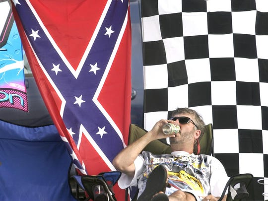 Race fan Charlie Ryan of Panama City Beach, Fla., is surrounded by various flags, including the Confederate flag, as he and friends relax in the camping area at the Indianapolis Motor Speedway on Aug. 2, 2003, before that year's Brickyard 400 race.