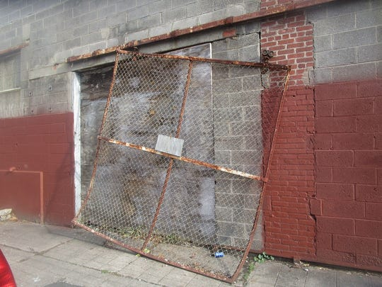 A rusted metal gate hanging perilously from the back side of the abandoned Leader Dye factory. Residents said the structure poses a hazard to neighborhood children.