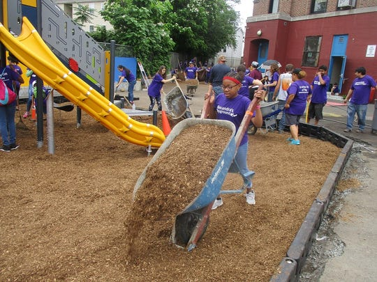 Fifth grader Rachel Muguit, dumps mulch from a wheelbarrow at the construction for the new playground at her school.