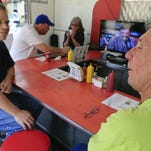 Brian Higdon, left, talks with Bob Anderson while the two wait for lunch at Coqui's Cafe, a small 10-seat diner that serves sandwiches, breakfast and Puerto Rican-infused food such as plantains and flan on the corner of Bank and Market Streets in New Albany. Behind the two is Michael Simon and friend Jan Powell. Simon likes the food.