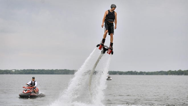 Flyboarder/hoverboarder Garrick Grace flies about 10 feet off the water during a demonstration of a Flyboard with Just Add Water Flyboard owner Joe Briant, who monitors his flight on a Sea Doo, at left, June 10 on Sugar Lake near Maple Lake. The device uses the water thrust from a personal watercraft to propel the rider into the air.
