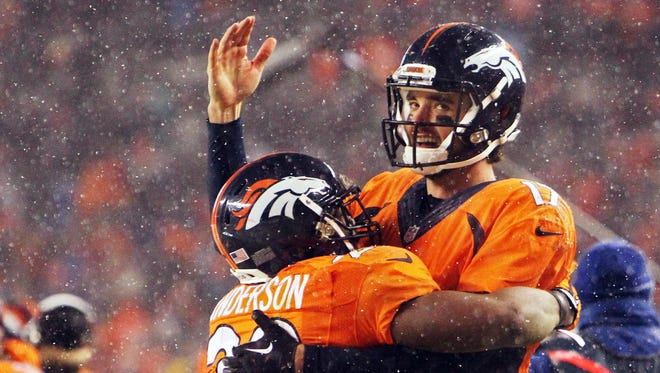Denver Broncos quarterback Brock Osweiler (17) and running back C.J. Anderson (22) celebrate during the second half against the New England Patriots at Sports Authority Field at Mile High.