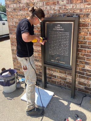 Danielle Robinson, instructor of Art and Design at Fort Hays State University, works on restoring a historical marker in downtown Hays.