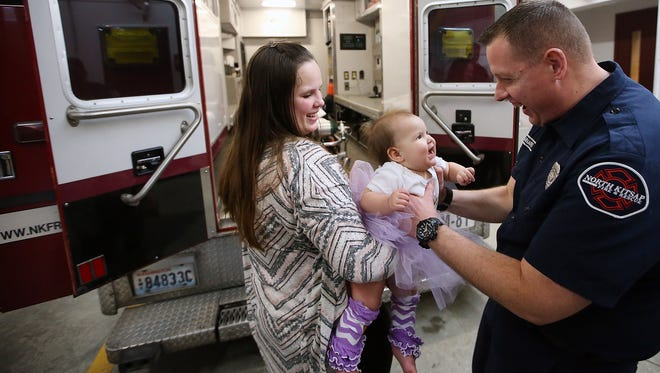 Craig Barnard, the North Kitsap Fire and Rescue paramedic who delivered baby Eleanor on Feb. 6, 2017, greets her on Tuesday at NKFR's Station 81. Barnard and the Medic 81 crew picked up Lakeisha from her home in Little Boston amid a snowstorm early on that February morning, but Eleanor didn't wait to get to the hospital before making her debut.