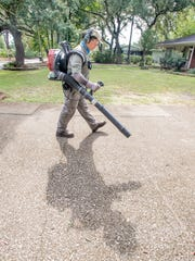 Eric Majors blows lawn debris from a driveway in Pensacola